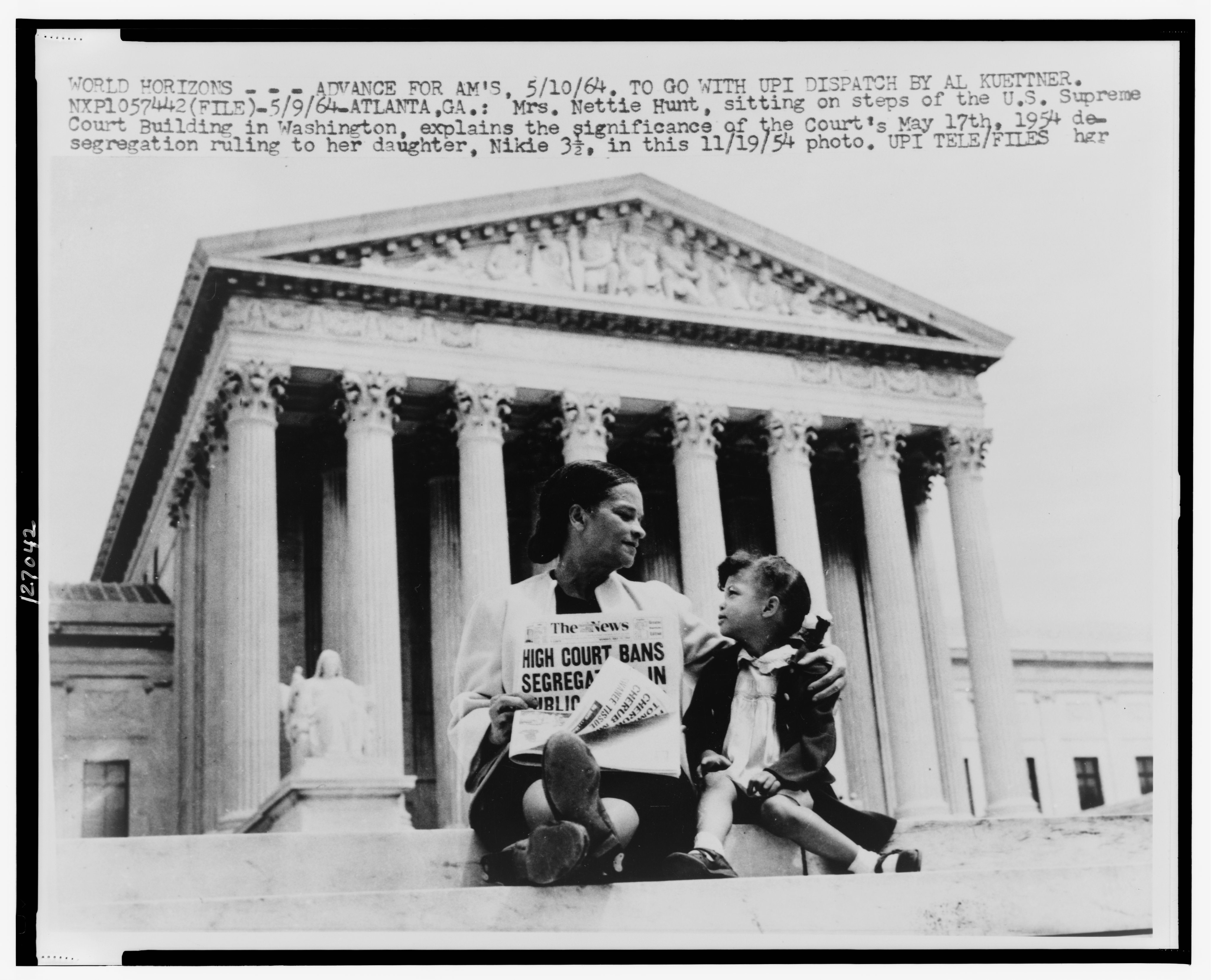Mrs. Nettie Hunt, sitting on steps of Supreme Court holding newspaper, explaining to her daughter Nikkie the meaning of the Supreme Courts decision banning school segregation, 1954. United Press International telephoto. Reproduced from the Collections of the LIBRARY OF CONGRESS.